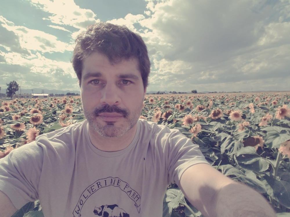 white man with mustache, in front of sunflower field
