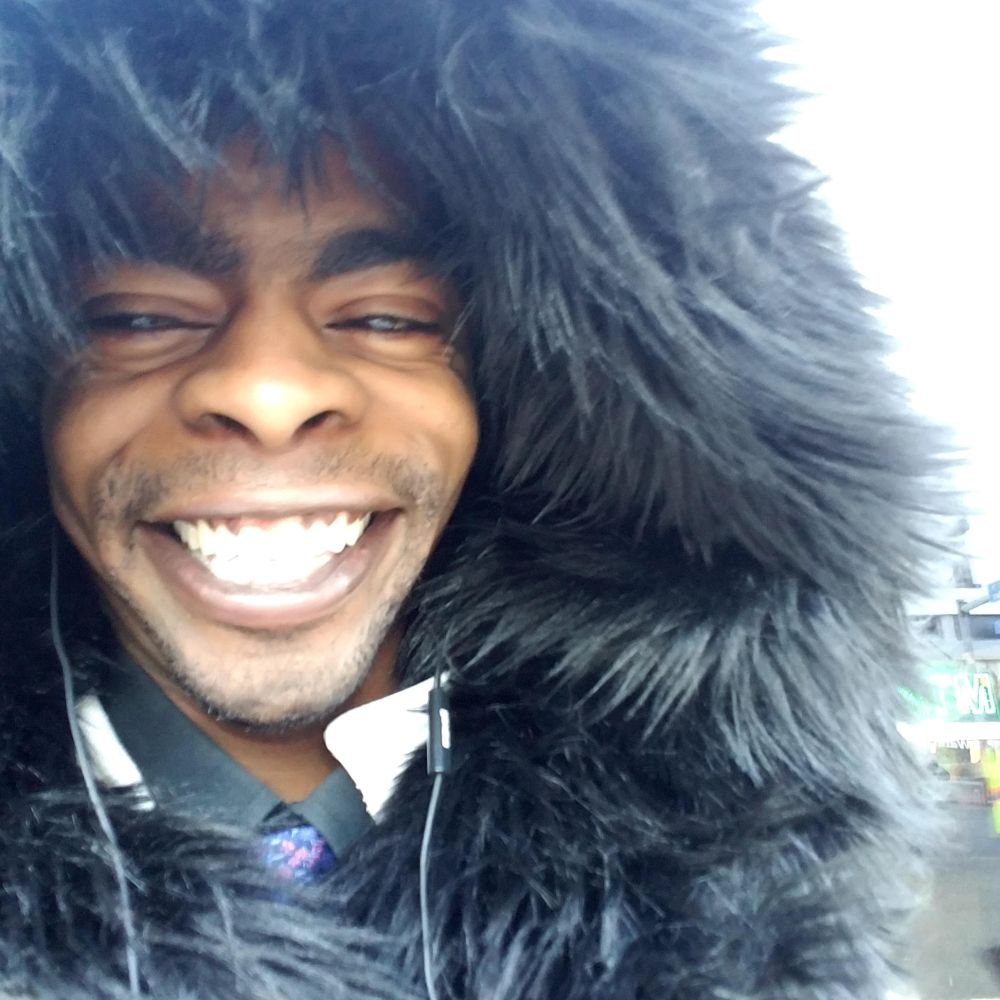 black man smiling, black furry hood