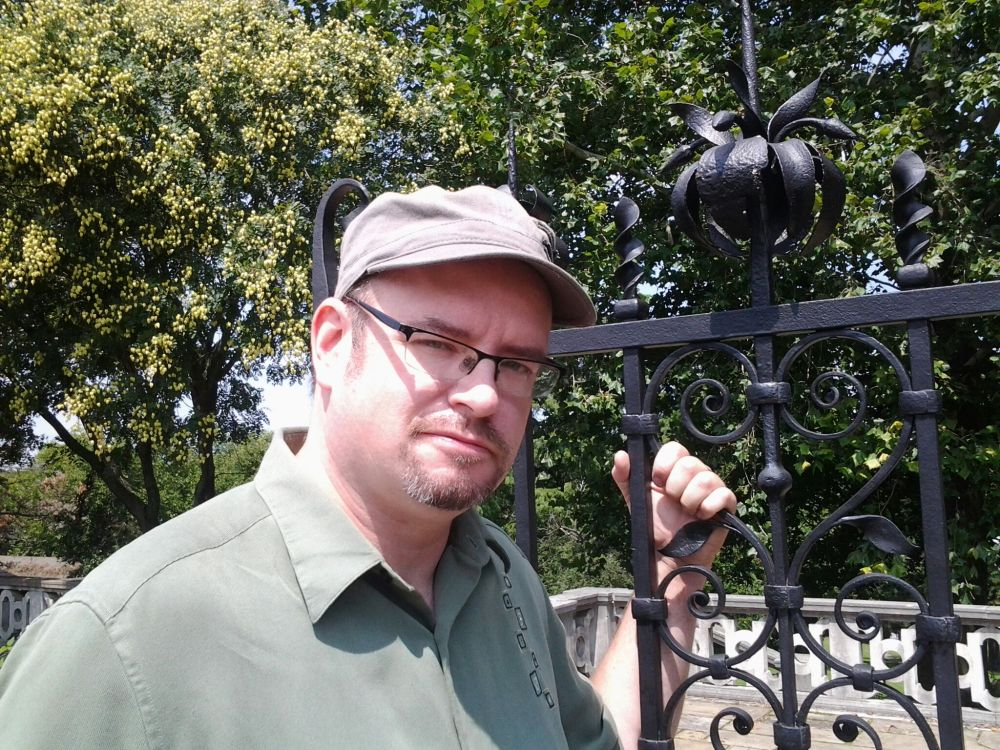 white man with glasses, standing in front of black fence